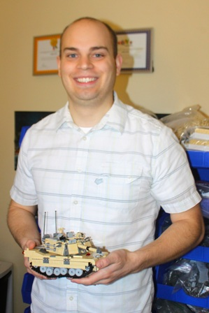 Andrew Roberts poses with a Lego M1 tank he designed and built.